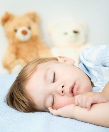Cute little boy is sleeping on a white pillow photo
