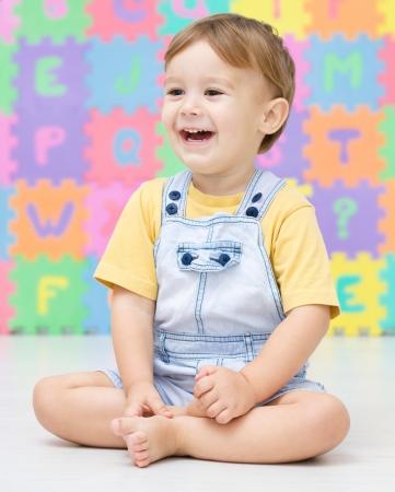 nursery education: Ni�o peque�o lindo est� sonriendo mientras est� sentado en el suelo Foto de archivo