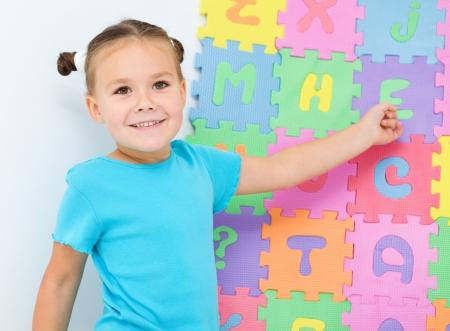 niños estudiando: La niña linda está mostrando la letra E del alfabeto en el preescolar