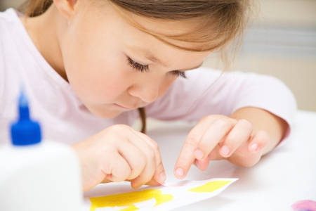 Cute little girl applying a color paper using glue while doing arts and crafts in preschool