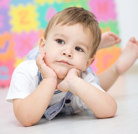 Portrait of a little boy who is laying on the floor photo