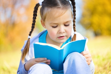 child reading: Cute little girl reads a book, isolated over white
