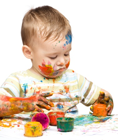 Portrait of a cute little boy messily playing with paints, isolated over white Stock Photo - 16120226