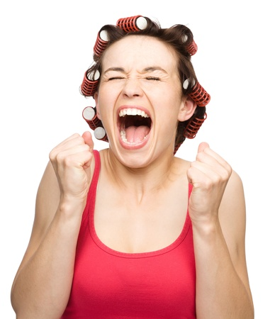 exhilarated: Young woman is screaming holding her fists tight while wearing hair-rollers, isolated over white