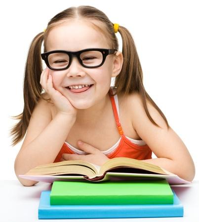 sacar la lengua: Linda niña alegre leer el libro mientras lleva gafas y sacando la lengua, aislado más de blanco