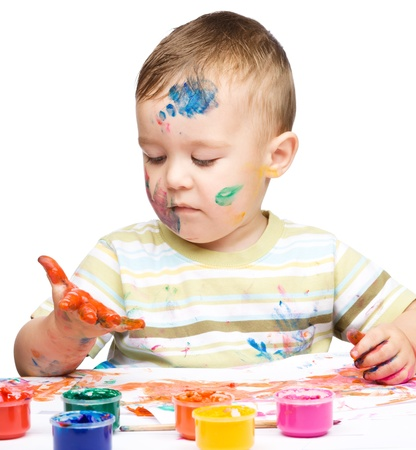 Portrait of a cute little boy messily playing with paints, isolated over white Stock Photo - 16336127