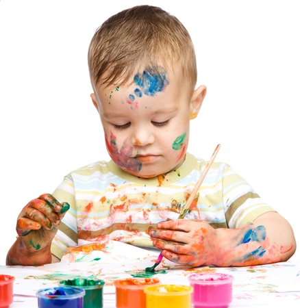 Portrait of a cute little boy messily playing with paints, isolated over white Stock Photo - 16336110