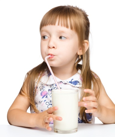 kids eating healthy: Cute little girl drinks milk using drinking straw, isolated over white