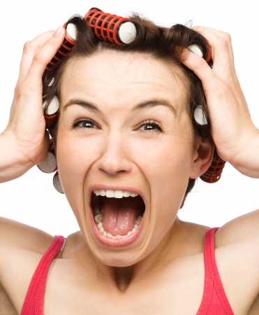 horribly: Young woman is screaming in terror holding her head with hands while wearing hair-rollers, isolated over white