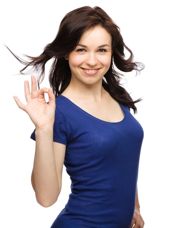 all smiles: Young woman dressed in blue is showing OK sign, isolated over white