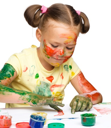 Portrait of a cute cheerful girl playing with paints, isolated over white Stock Photo - 16336154
