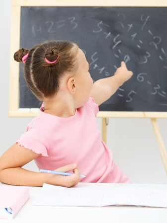 Cute little girl is showing something on blackboard in preschool photo