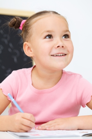 Cute little girl is writing using a pen in preschool photo