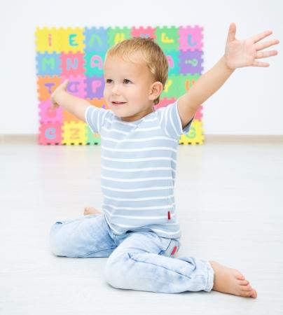 Cute little boy alzò le mani, mentre seduta sul pavimento Archivio Fotografico
