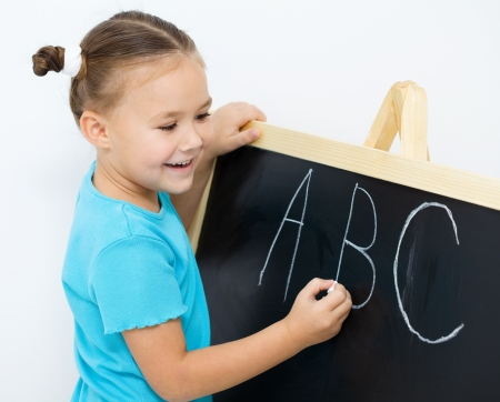 Cute little girl is writing letters on a blackboard in school
