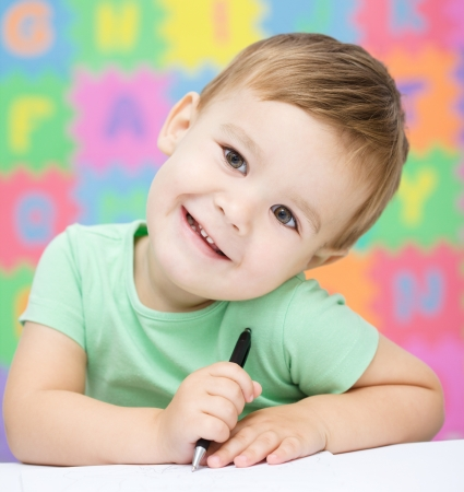 writing activity: Cute little girl is writing using a pen in preschool Stock Photo