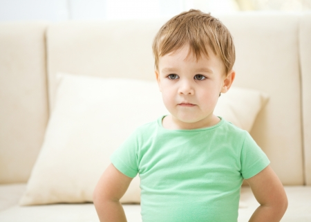 Cute little boy is standing in front of a sofa photo