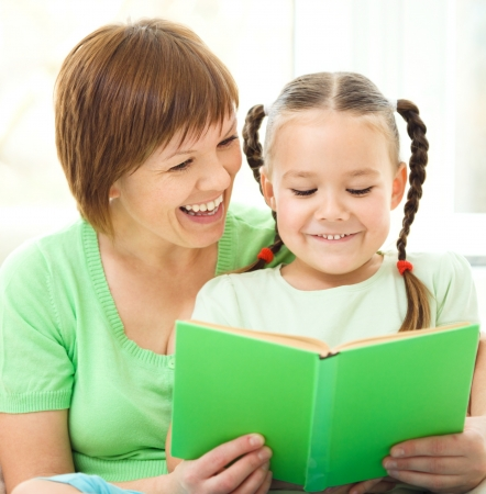 Mother is reading book for her daughter, indoor shoot Stock Photo - 16382627