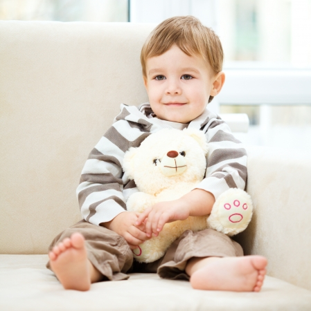 Little boy is holding his teddy bear while sitting on a sofa photo