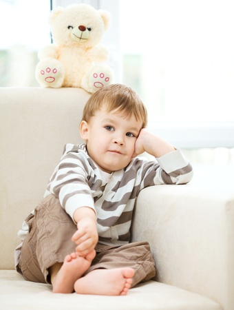 Portrait of a little boy sitting on white sofa photo