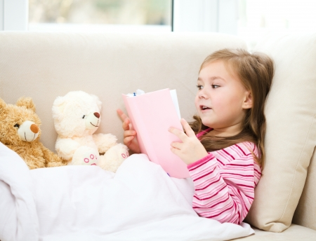 Little girl is reading a book for her teddy bears while laying on white couch photo