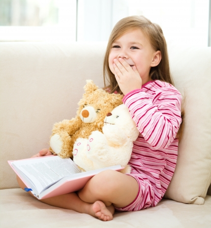 Little girl is reading a book for her teddy bears while sitting on white couch photo