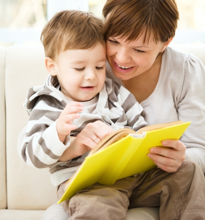 Mother is reading book for her son, indoor shoot Stock Photo - 16382643