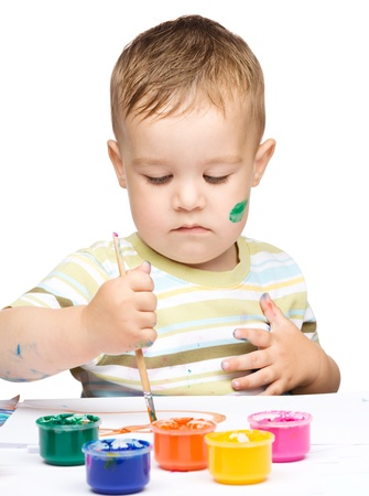 Portrait of a cute little boy messily playing with paints, isolated over white photo