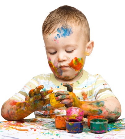 Portrait of a cute little boy messily playing with paints, isolated over white Stock Photo - 16521843