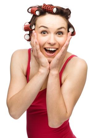 astonishment: Mujer joven est� sosteniendo su cara de asombro mientras llevaba el cabello, rodillos, aislado m�s de blanco Foto de archivo