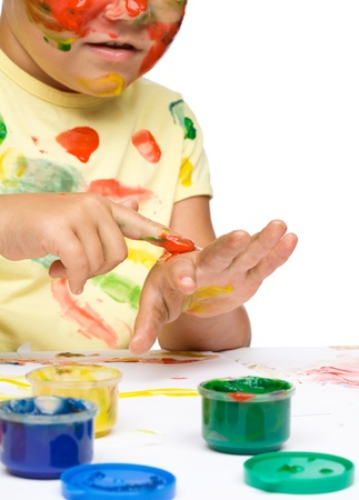 Portrait of a cute cheerful girl playing with paints, isolated over white Stock Photo - 16521845