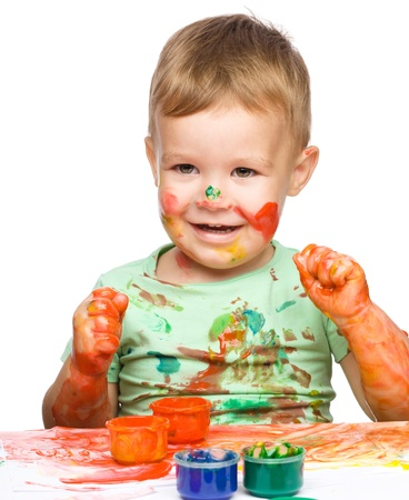 Portrait of a cute little boy playing with paints clenching his fists in joy, isolated over white Stock Photo - 16521814