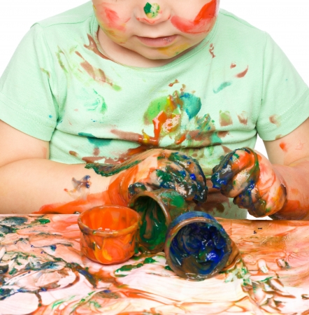 Portrait of a cute little boy messily playing with paints, isolated over white Stock Photo - 16521853