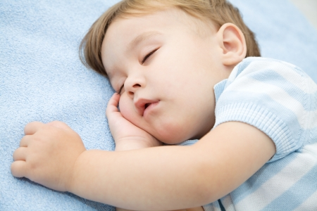 Portrait of a cute little boy sleeping on white pillow photo