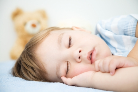 drowse: Cute little boy is sleeping in front of his teddy bear