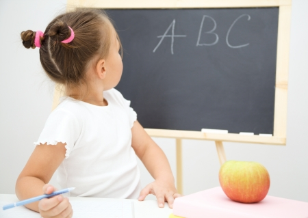 Cute little girl is studying in school, looking at something on blackboard photo