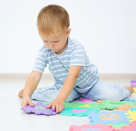 Little boy is putting together a big puzzle while sitting on the floor photo