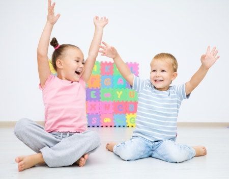 Cute children are sitting on floor in preschool rising their hands up Imagens
