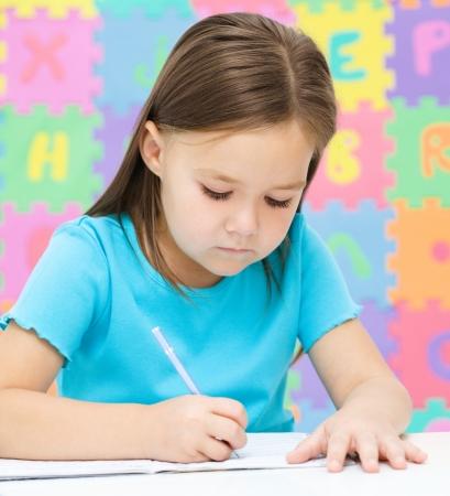 niños escribiendo: La niña linda está escribiendo con un bolígrafo