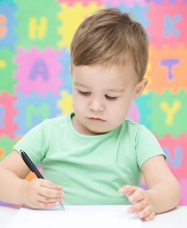 niños escribiendo: Niño pequeño que está escribiendo en su cuaderno en el preescolar