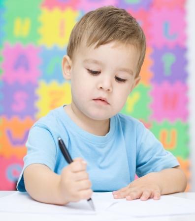 Niño pequeño que está escribiendo en su cuaderno en el preescolar Foto de archivo - 16521809