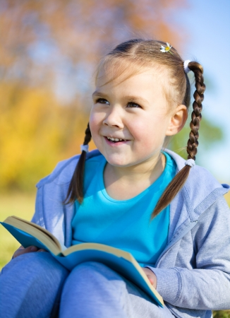 Cute little girl is reading a book outdoors photo