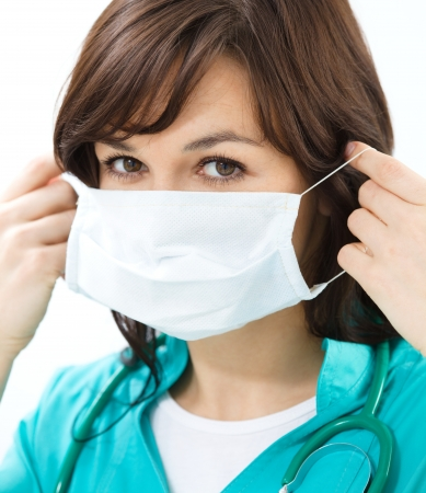 medical mask: Portrait of a woman in doctor uniform wearing surgical mask