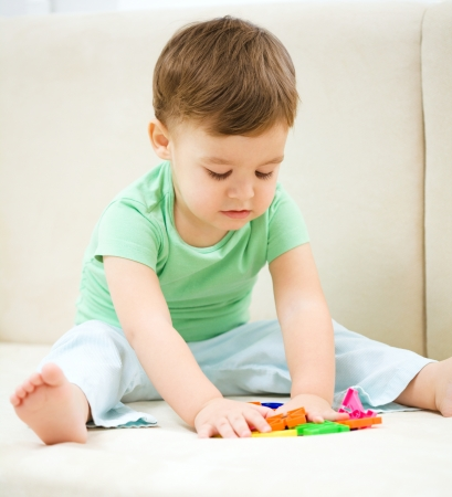 toddler playing: Cute little boy playing with toys while sitting on a couch, indoor shoot