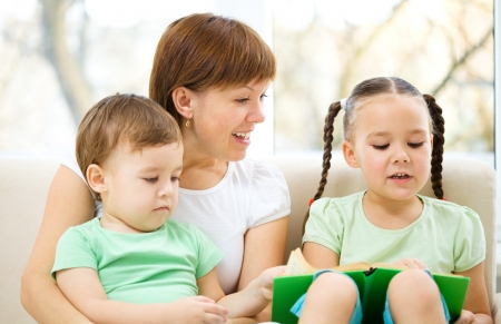 Family is reading book while sitting on a couch, indoor shoot Stock Photo - 16521869