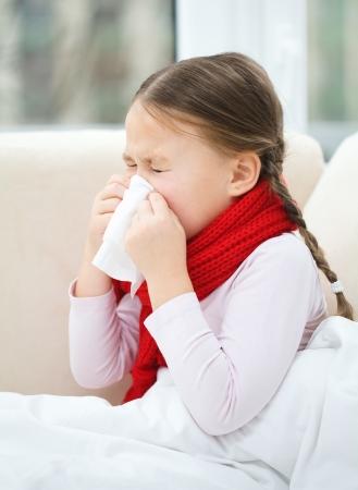 niños enfermos: Niña sopla su nariz mientras se está sentado en un sofá