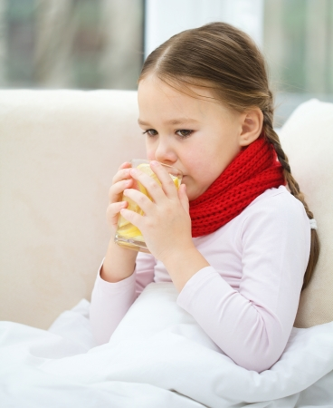 Ill little girl is grinning vitamin cocktail while sitting on a sofa Stock Photo - 16521803
