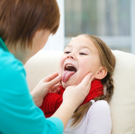Doctor is examining a little girl who showing tongue, indoor shoot Stock Photo