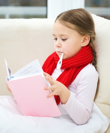 Ill little girl is sitting on sofa with thermometer in her mouth and reading book Stock Photo - 16521806