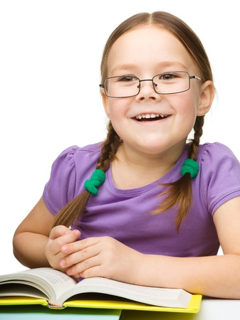 Cute little girl is reading a book while wearing glasses, isolated over white Stock Photo - 16695874